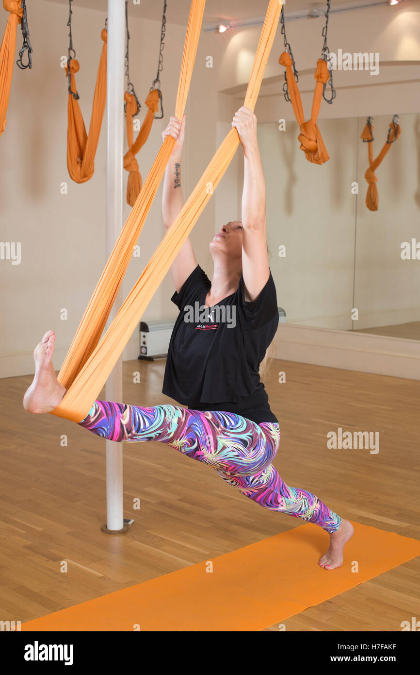 man taking part in aerial yoga class with woman instructor hanging in yoga position in yoga hammock stock photos  u0026 yoga hammock stock images   alamy  rh   alamy