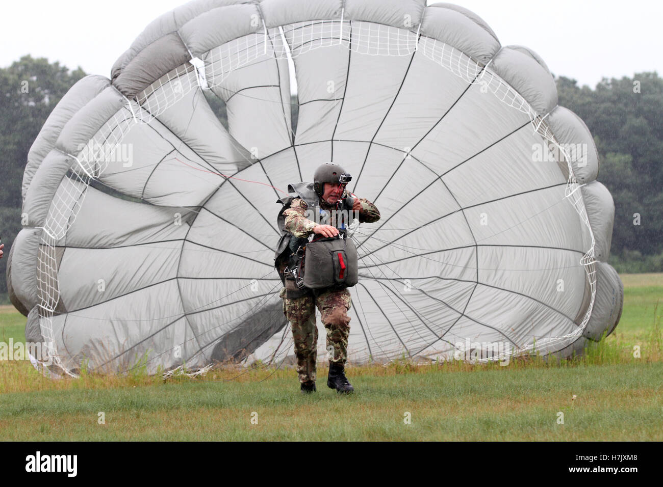 An Italian paratrooper soldier pulls his inflated parachute canopy while running to an X on the & An Italian paratrooper soldier pulls his inflated parachute canopy ...