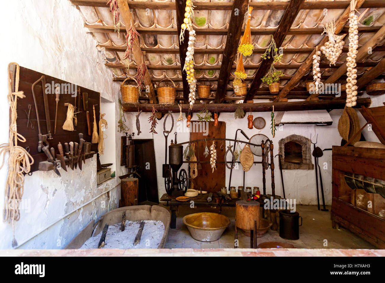 Old Fashioned Kitchen With Ancient Dishes And Hanging Garlic And Onion