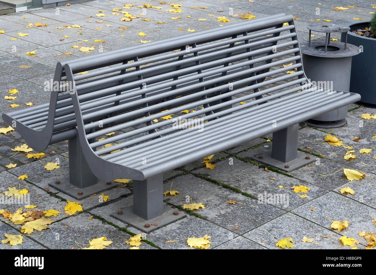 modern metal bench and recycle bin in the autumn city park stock  - modern metal bench and recycle bin in the autumn city park