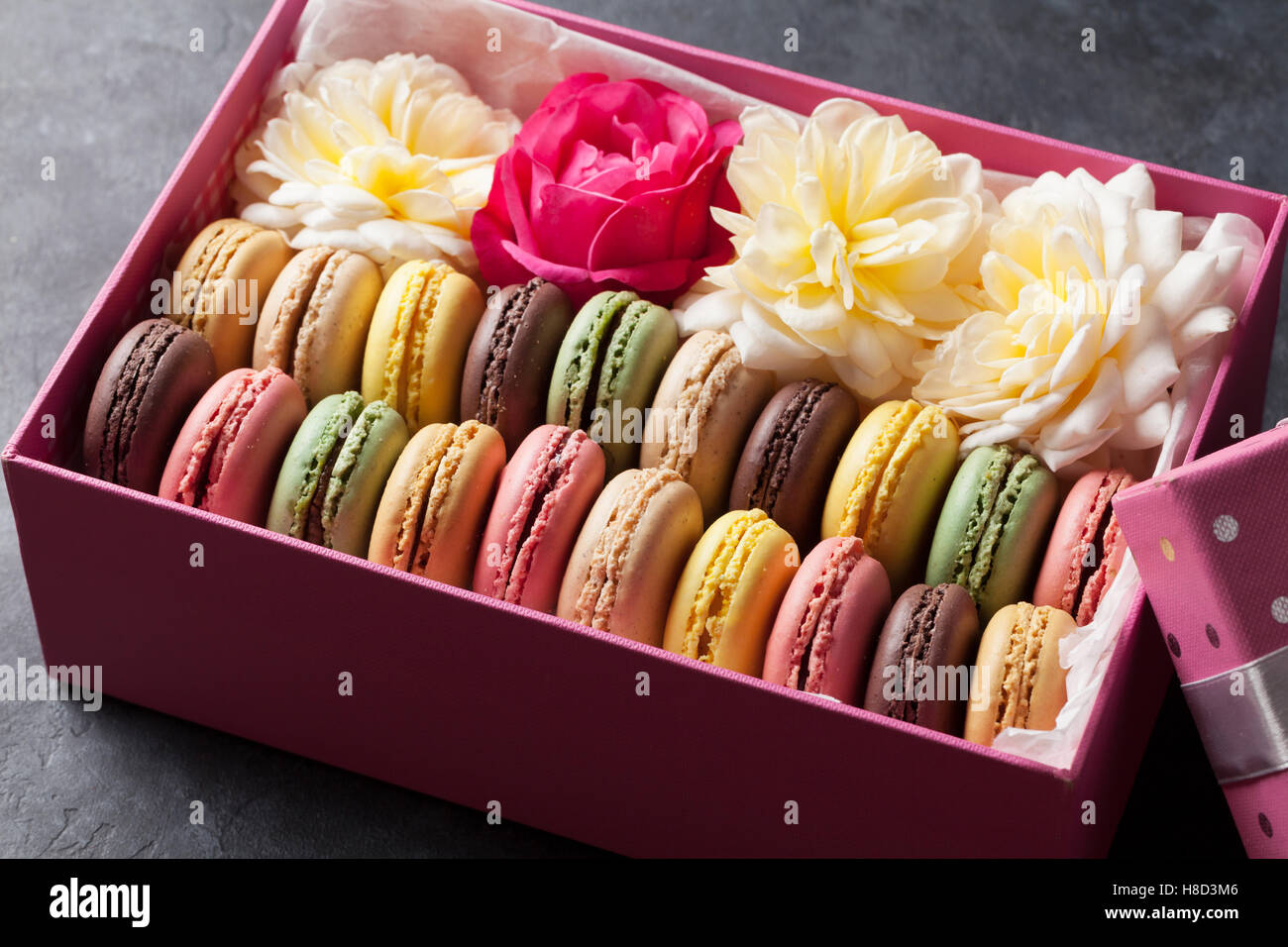 Colorful macaroons and flowers on stone table. Sweet macarons in ...