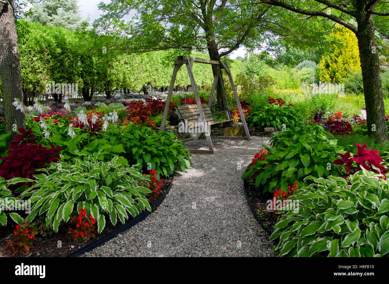 Horizontal Wooden Swing At Pineland Garden With Hostas And Coleus Along  Shaded Pathway, Maine, USA