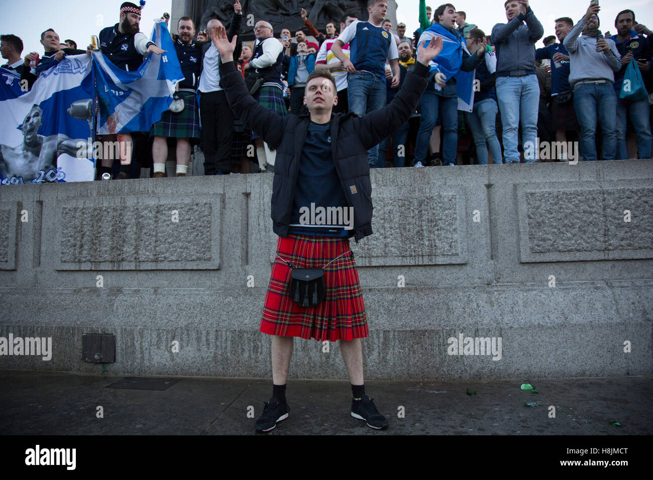 scotland fans wearing kilts in joyous mood drinking and singing