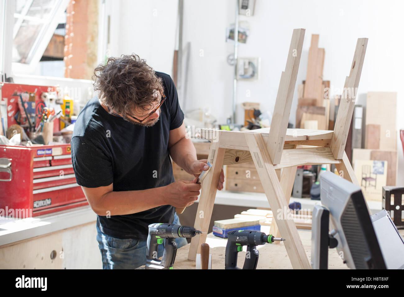Furniture designer maker working in his workshop. Furniture designer maker working in his workshop Stock Photo