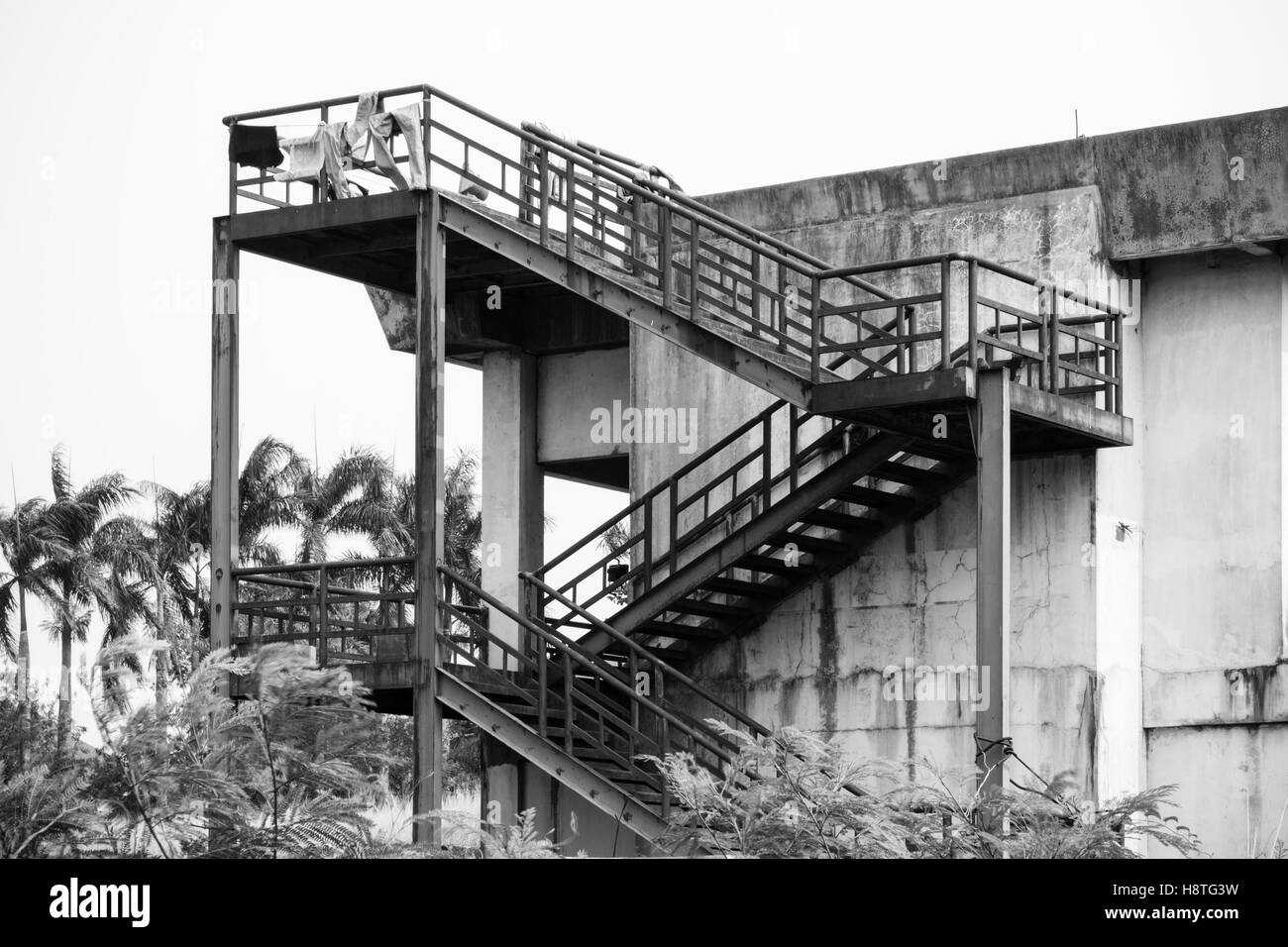 Metal Staircase Construction Which Made From Steel Platform Beside Of An  Abandoned Building. Black And White Photography.