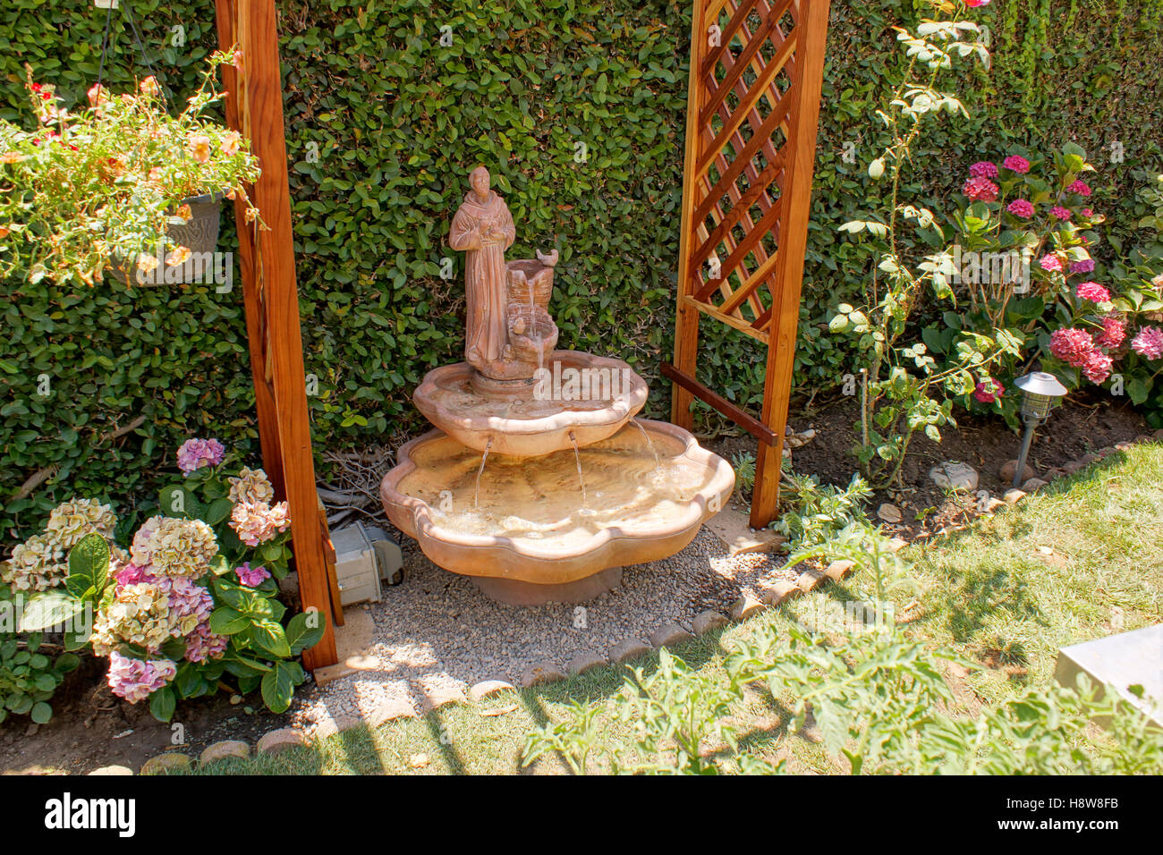 saint francis of assisi statue in a backyard water fountain stock