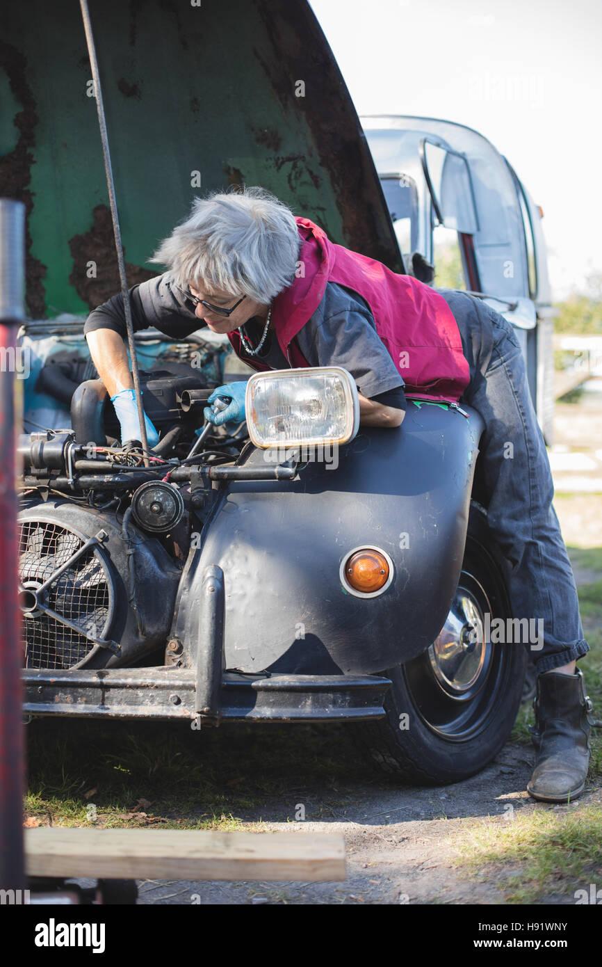 Elderly car mechanic working on her vintage car Stock Photo ...