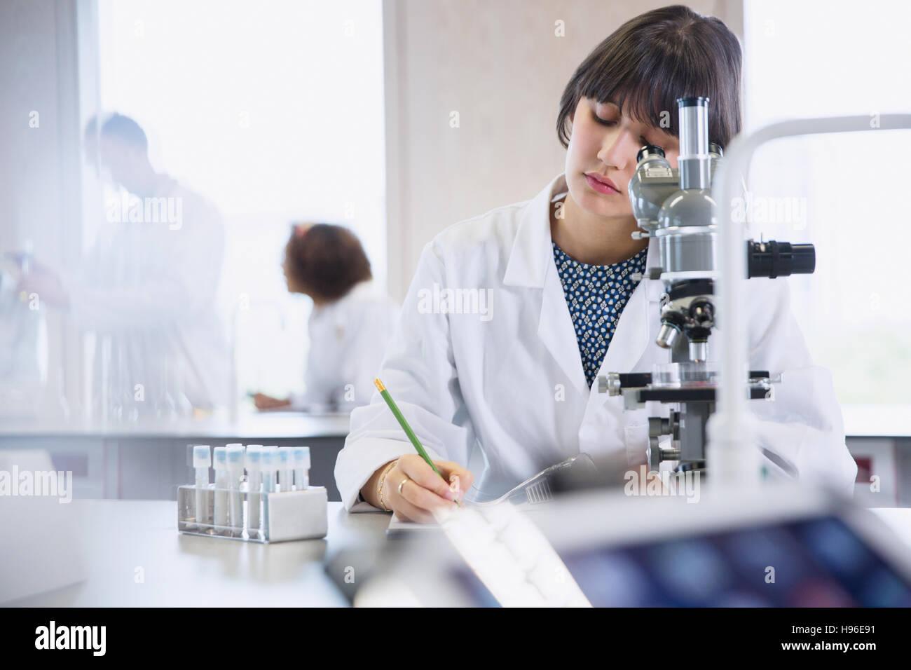 Female college student conducting scientific experiment in science ...
