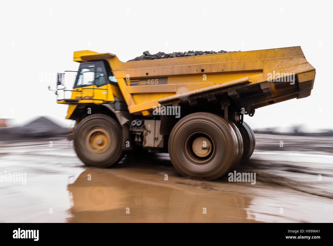 A kubota 465 rock dumper truck takes a full load of stone in a quarry in heavy rain