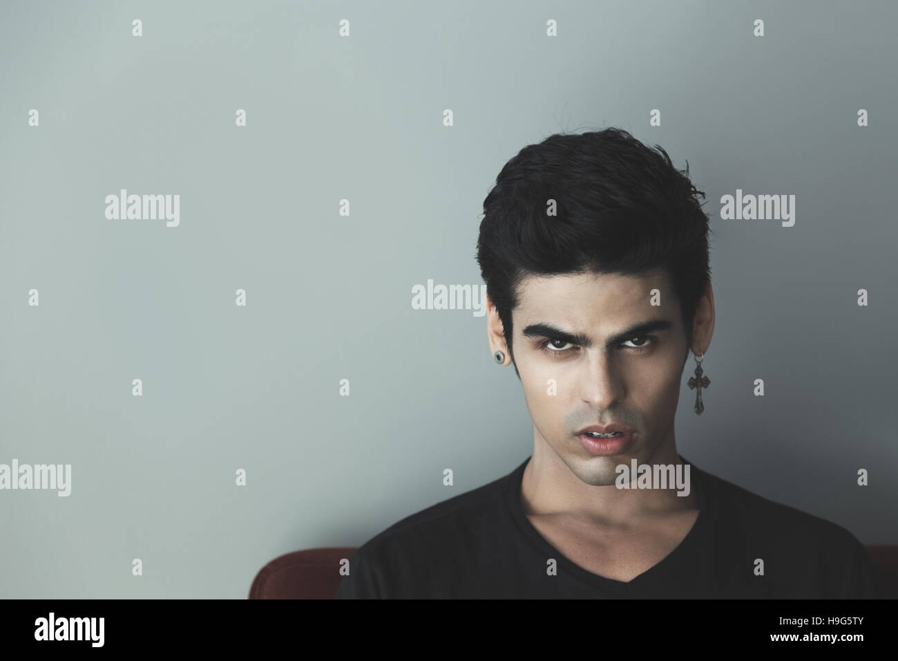 Portrait of attractive modern young white brazilian guy with black ...