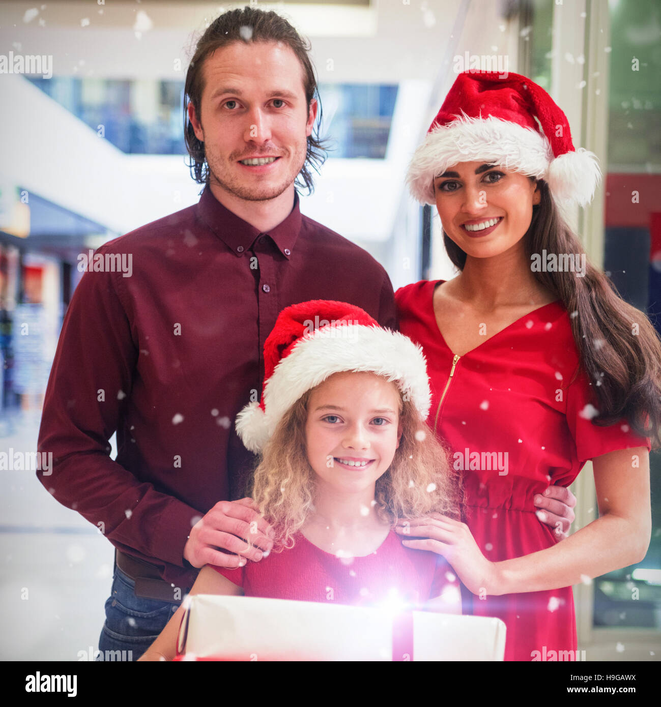 Composite image of portrait of family in christmas attire standing ...