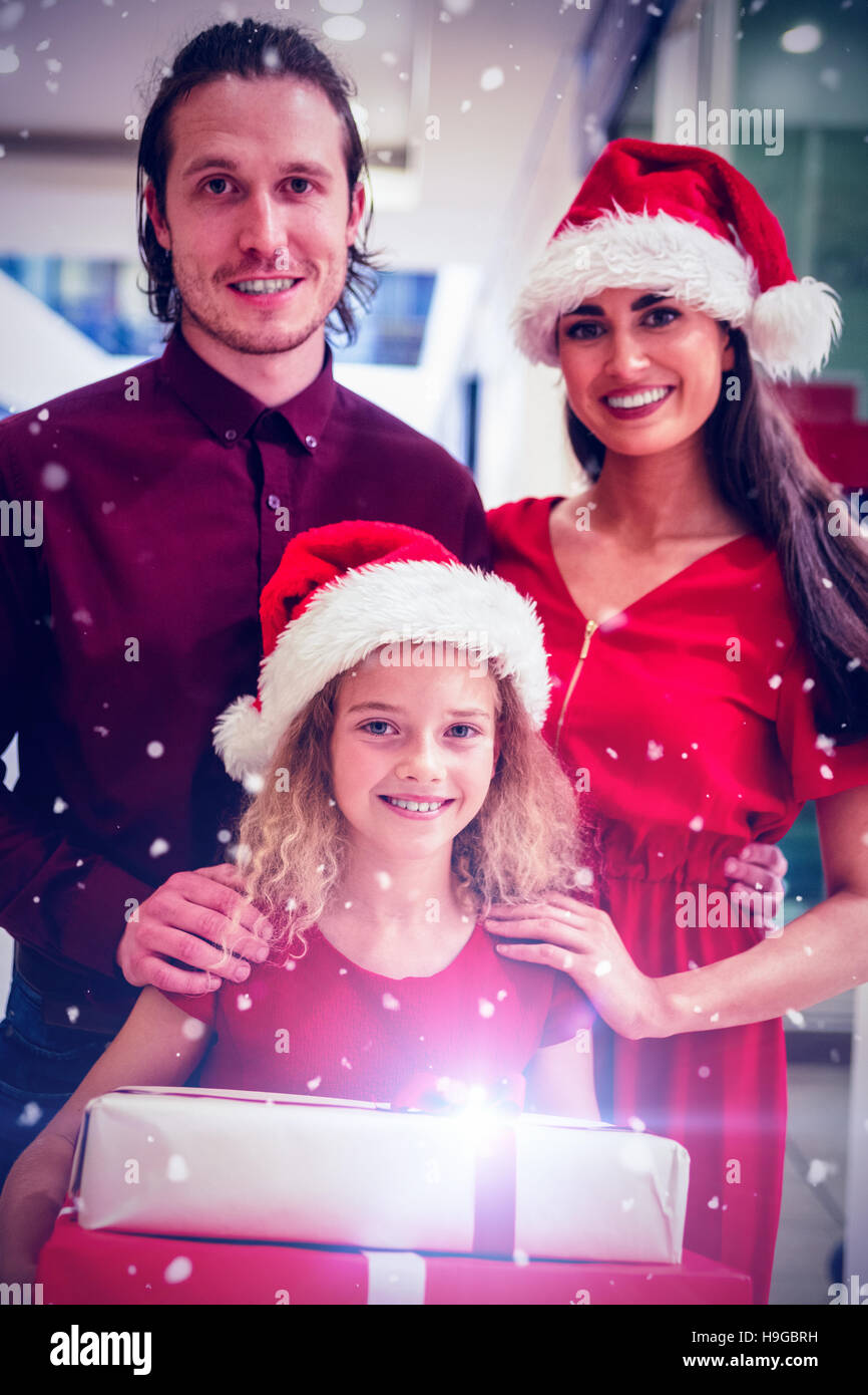 Composite image of family in christmas attire standing with ...