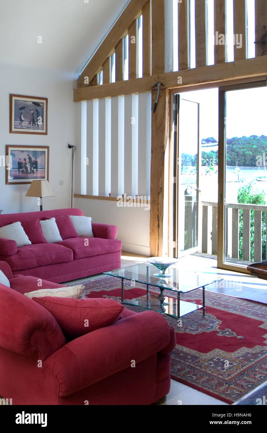 Barn Conversion Doors interior, red sofas, glass doors onto wood balcony, barn