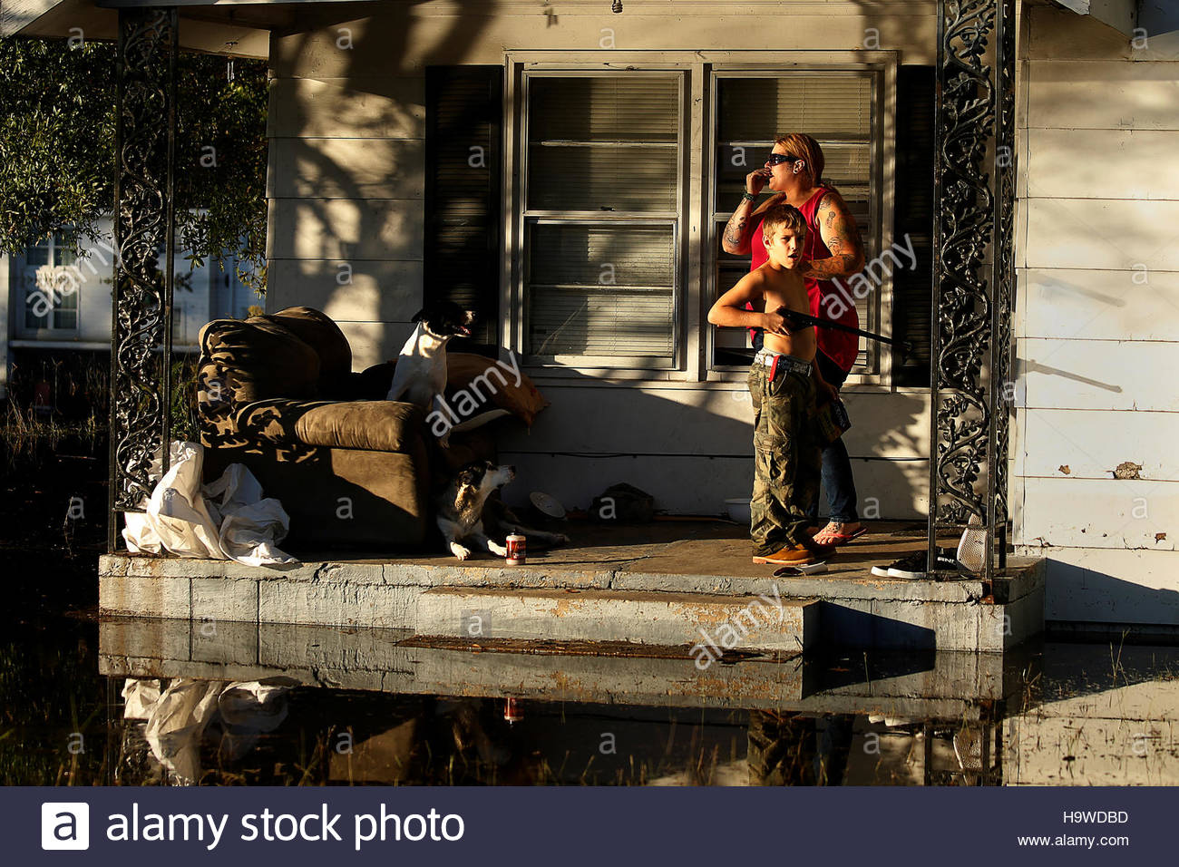 Residents hang out on their front porch as a child holds a bb gun while they seek refuge from flood waters as a result of hurricane matthew in lumberton