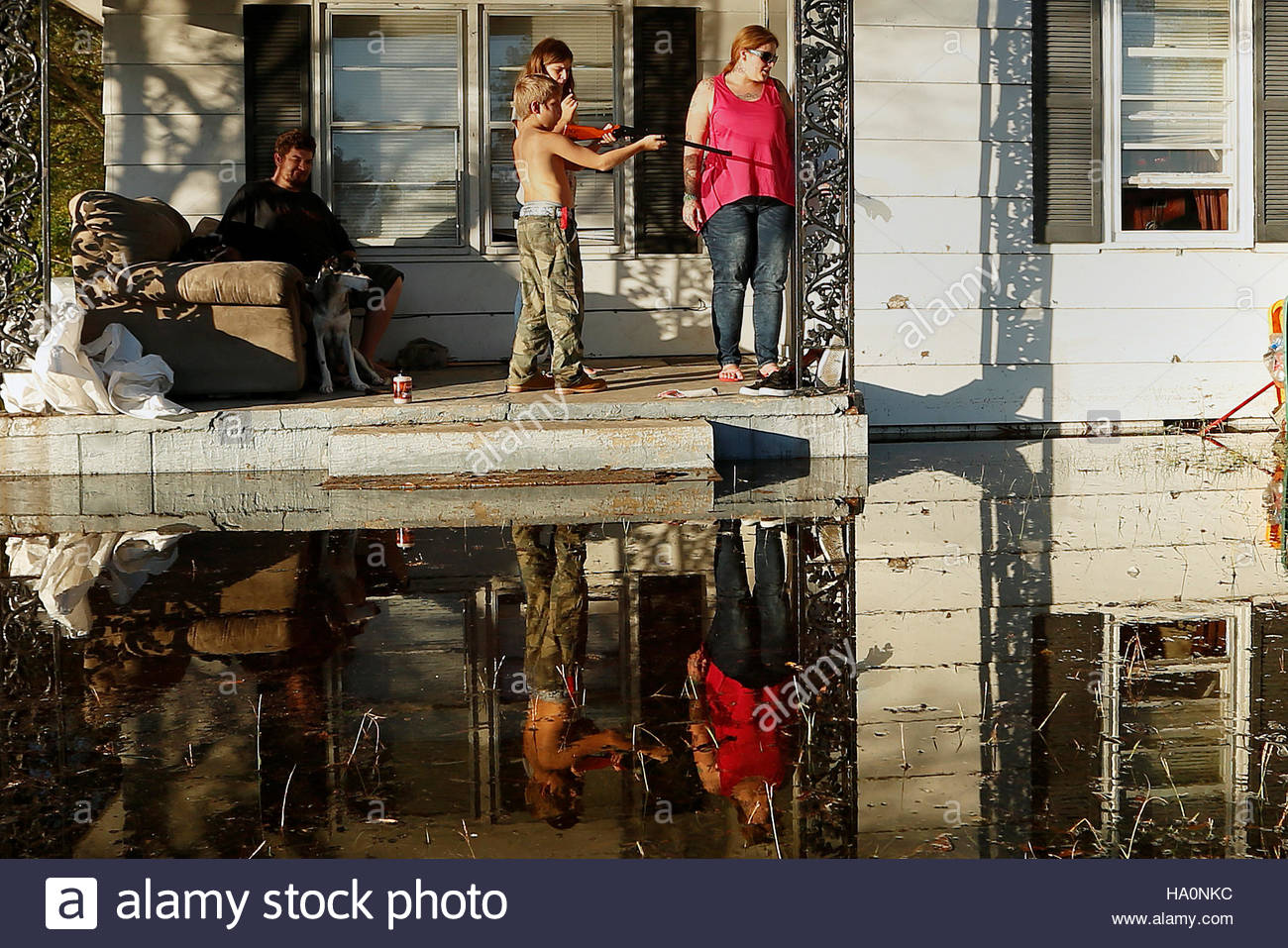 Local residents gather on their front porch as a child shoots a bb gun while they