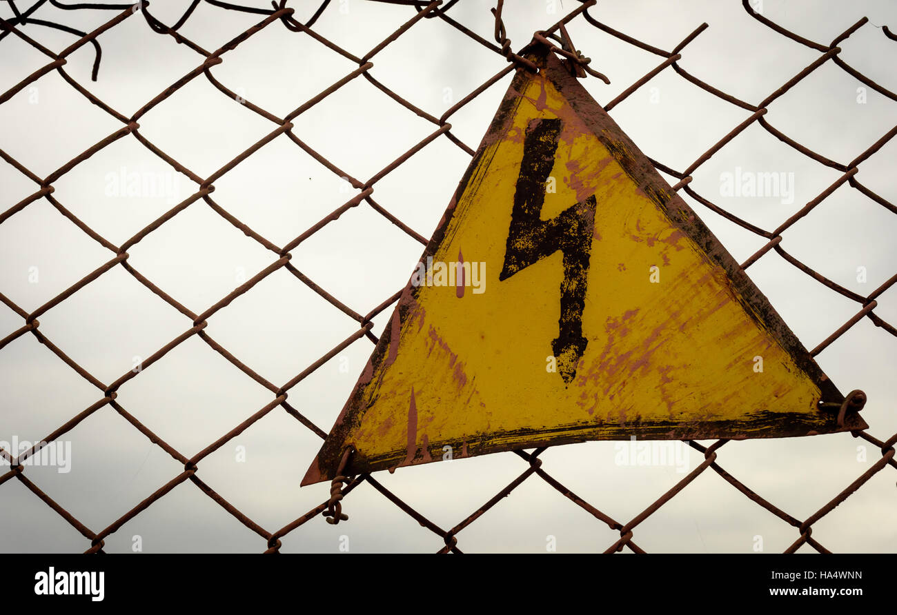 Warning sign electricity lightning bolt stock photos warning lightning bolt electricity warning sign in a yellow triangle set against a dark sky wire mesh buycottarizona