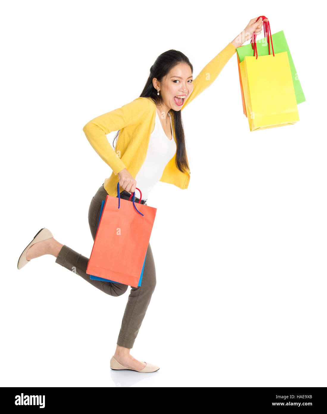 Woman posing with shopping bags isolated on white background full - Happy Young Asian Female Shopper Running Hands Outstretched Holding Shopping Bags And Smiling Full Length Isolated Standing On White Background