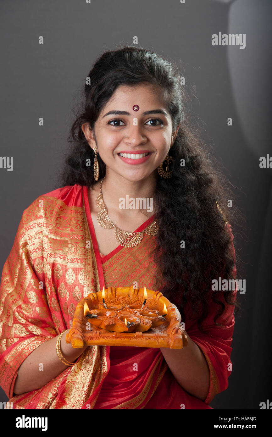 a girl smiling and holding a traditional Diwali oil lamp diya ... for Girl Holding Lamp  131fsj