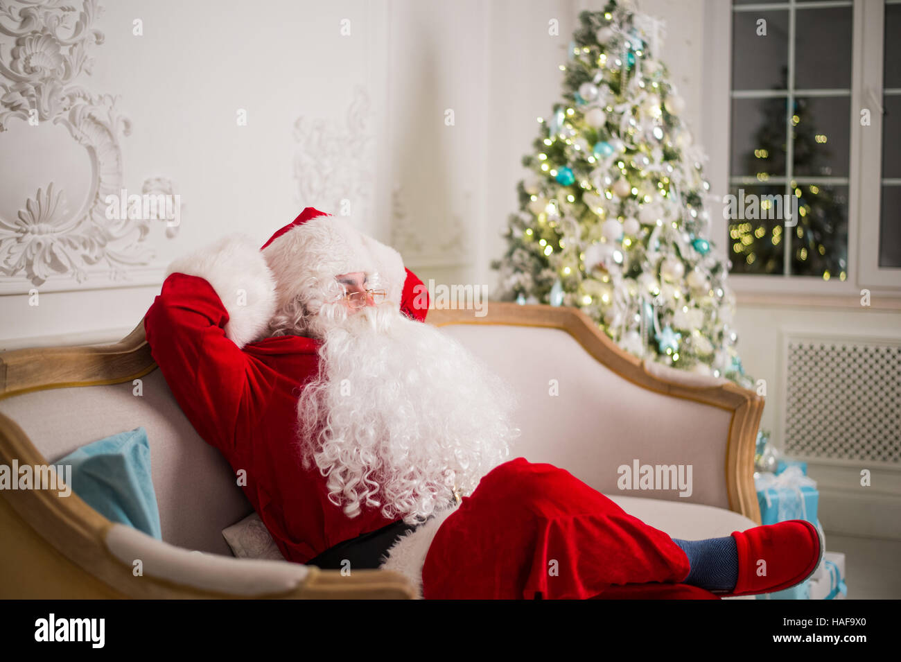 Santa claus relaxing on sofa against christmas tree at