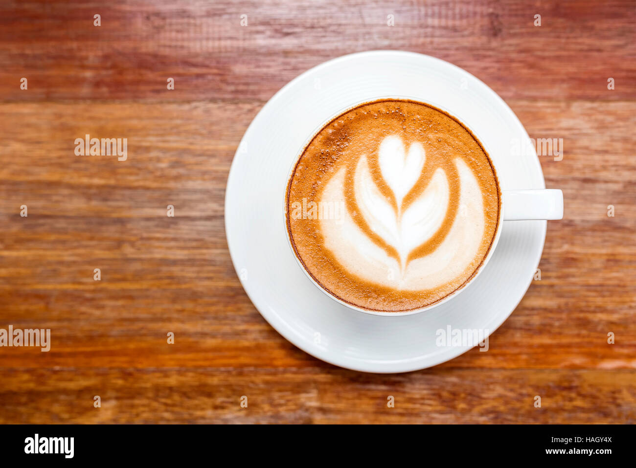 Cup of hot latte art coffee on wooden tabletop view stock photo cup of hot latte art coffee on wooden tabletop view geotapseo Gallery