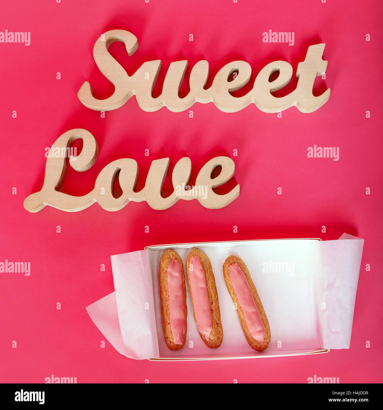 Words sweet love, wooden letters on pink paper with open box of fresh  cupcakes.