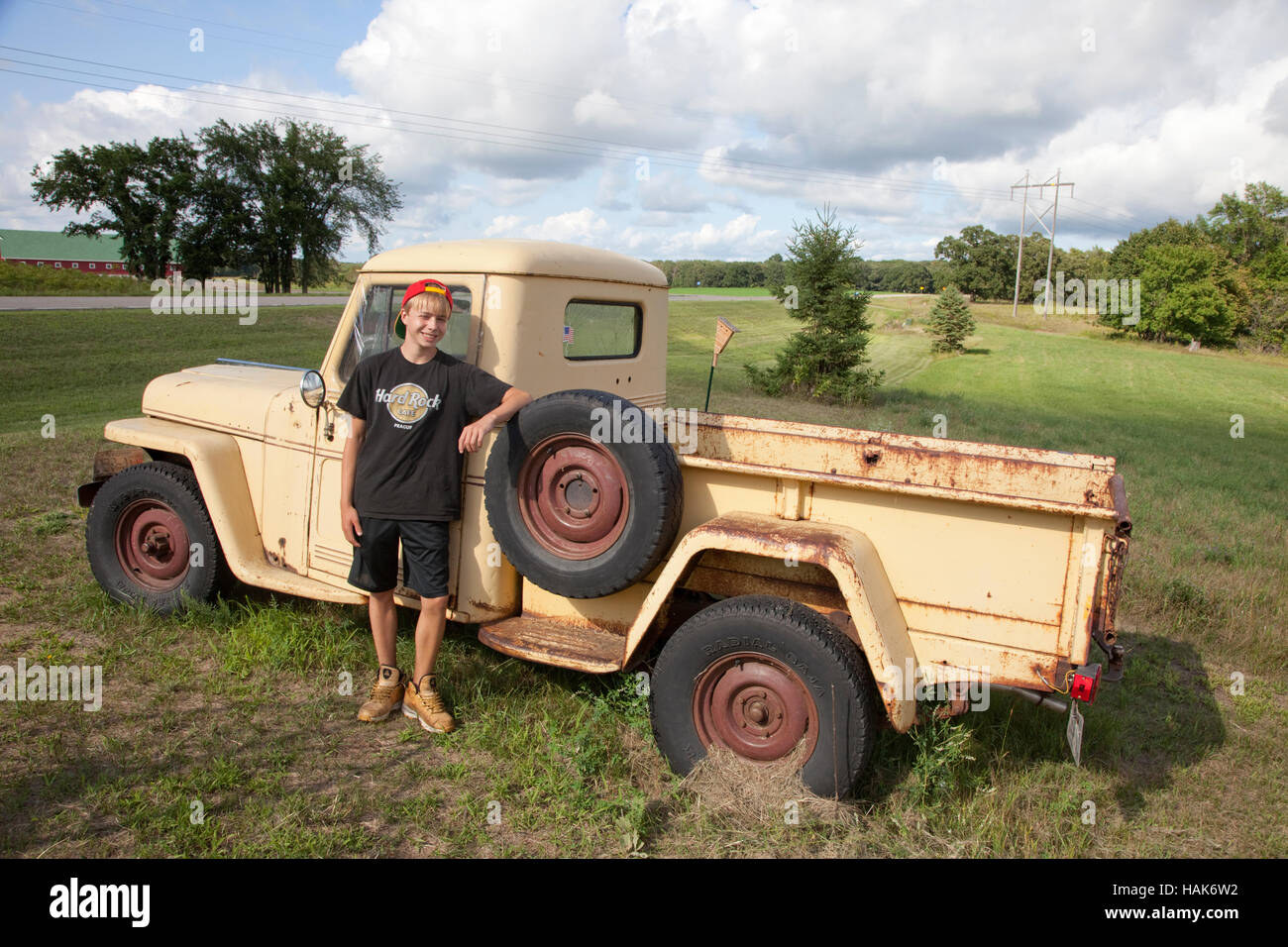 Young teen standing beside old vintage Willys Jeep Pickup Truck ...