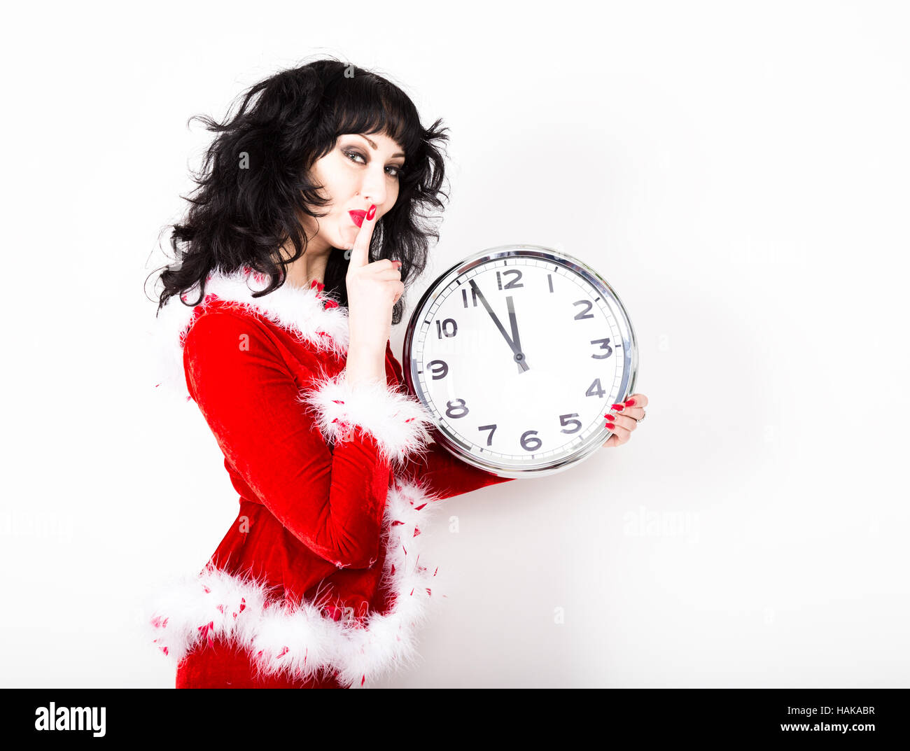 young beautiful woman in red coat holding big clock. time concept ...