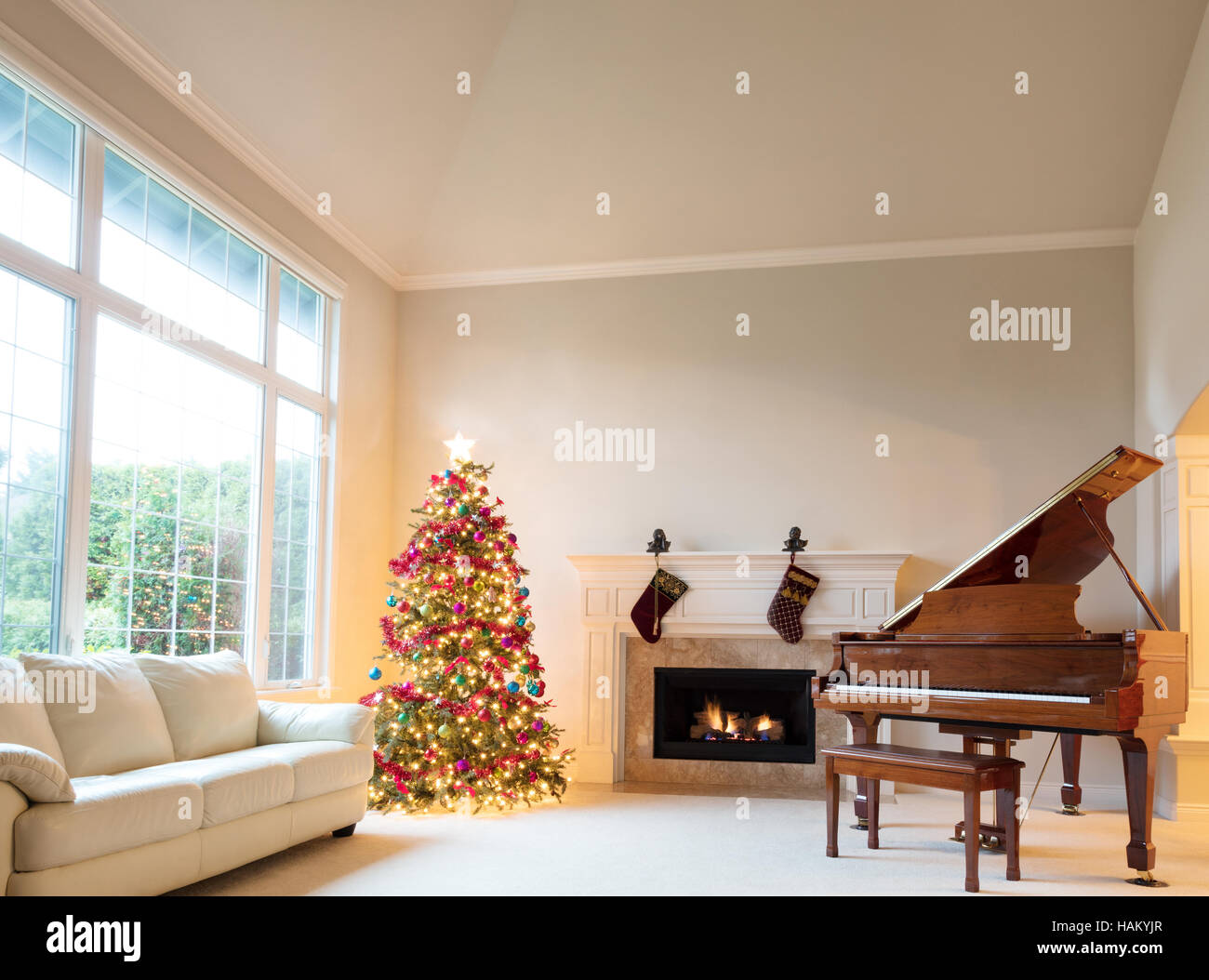 Christmas Tree In Living Room With Burning Fireplace And Grand Piano During Bright Day Time