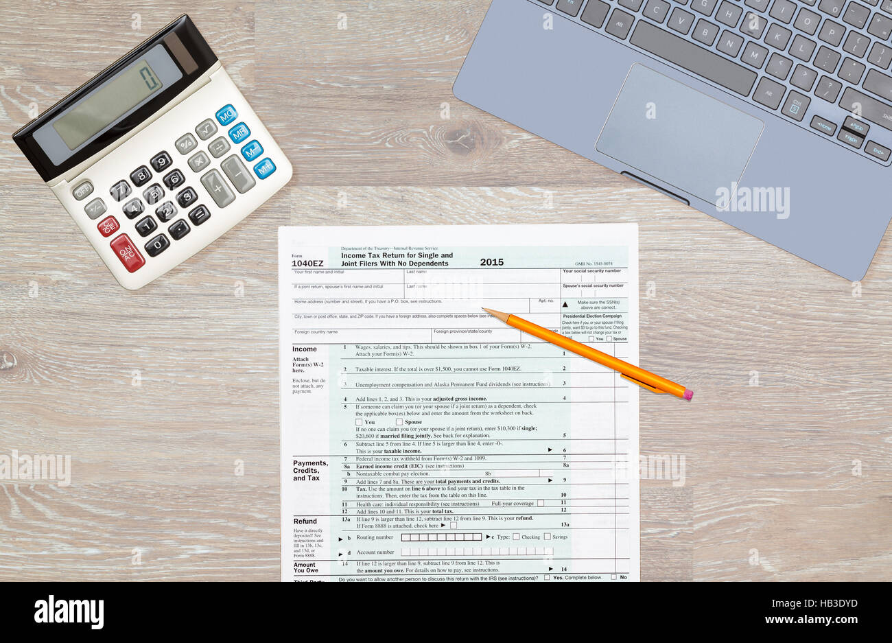 Laptop and calculator on 2015 irs form 1040ez stock photo royalty laptop and calculator on 2015 irs form 1040ez falaconquin