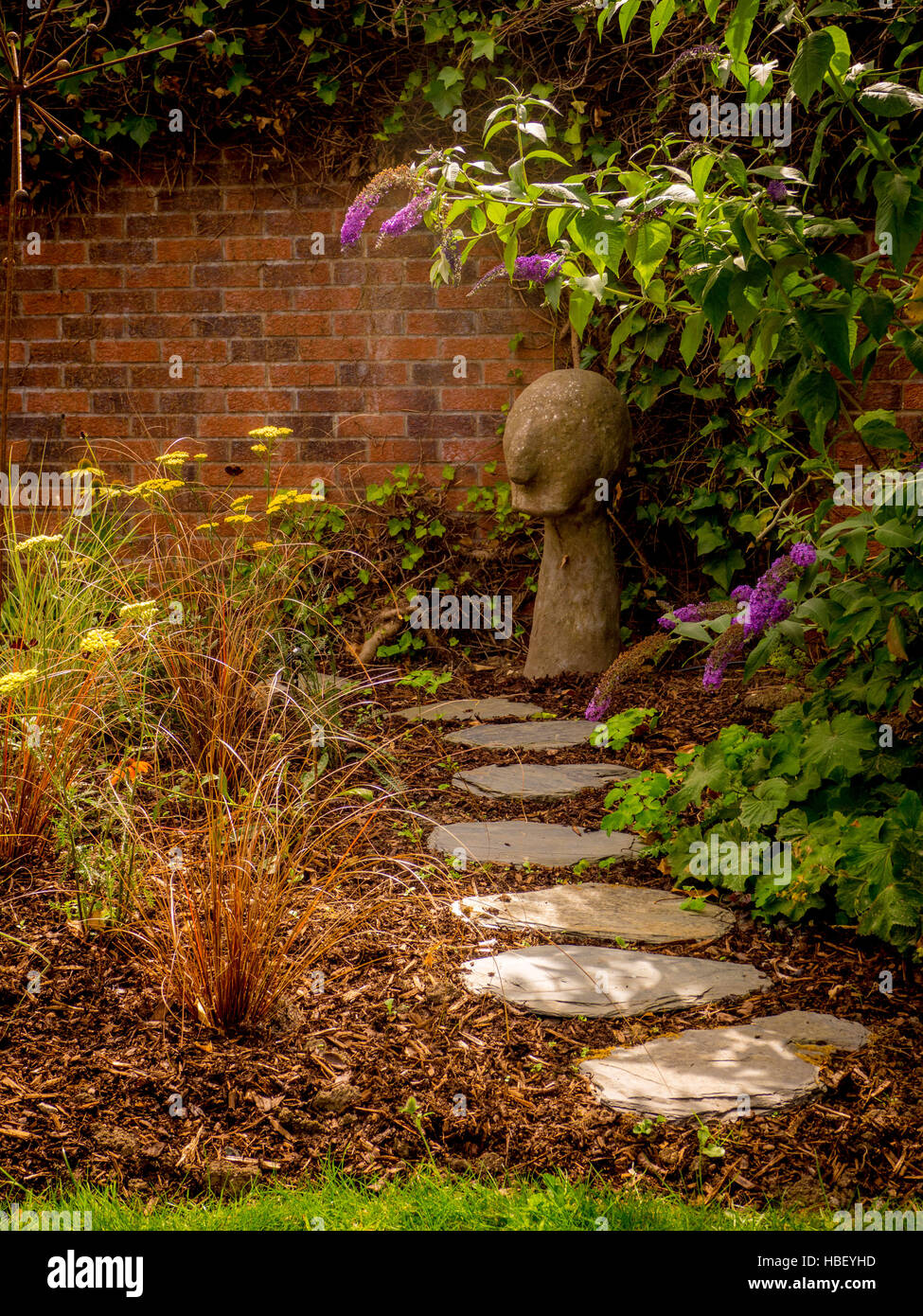 Stepping Stone Path Through Garden Flower Bed With Bark Chippings And Brick  Wall