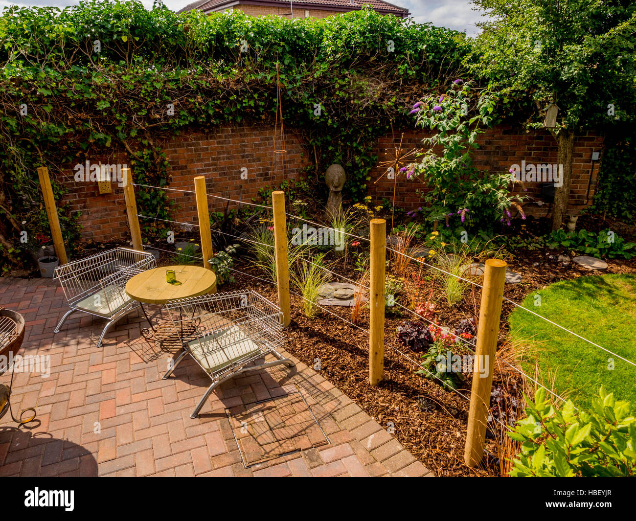 Modern Contemporary Walled Garden; Garden Areas Divided Using Wooden Stakes  To Create Outdoor Rooms In Modern Contemporary Design   Stock