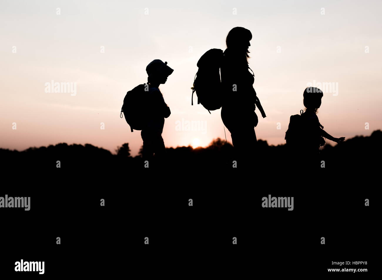Silhouette Of Family Hiking At Sunset Happy On Summer Vacation In Mountains Mom And Kids Carry Backpacks Travellers Walking Cliff Edge S