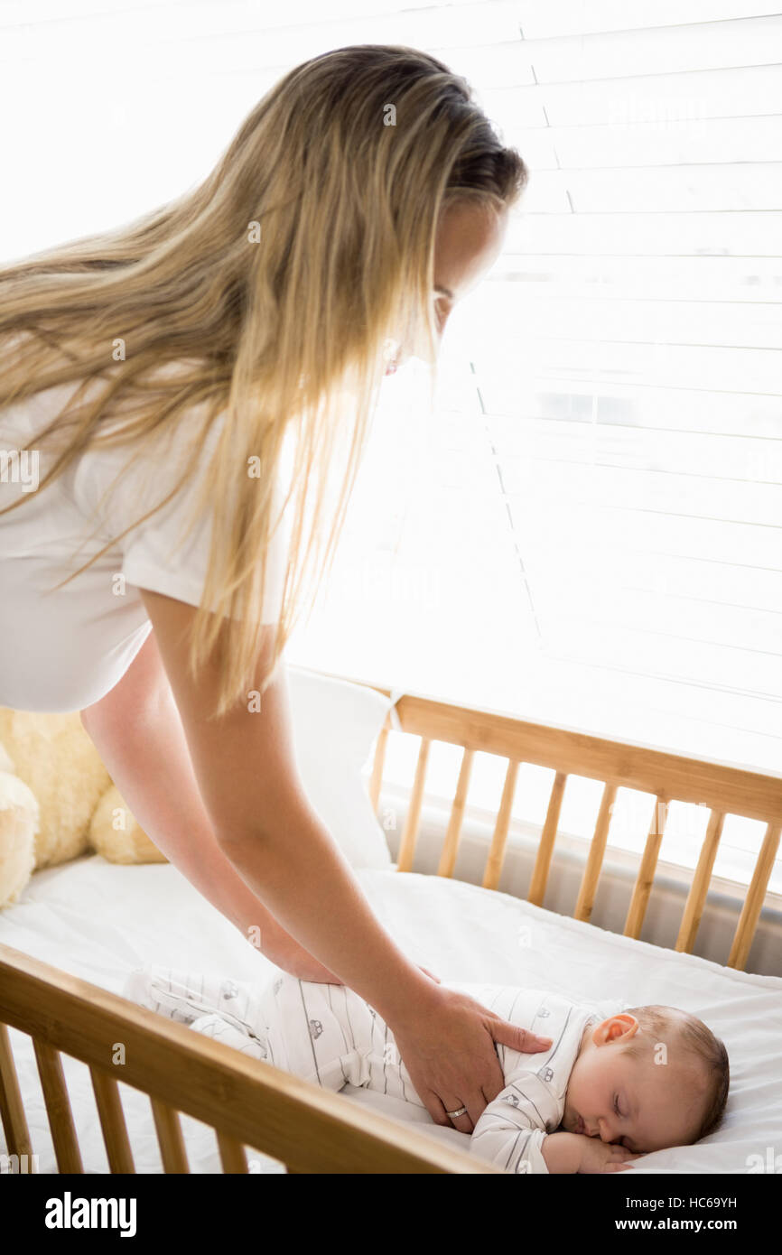 Baby bed next to mom - Mom Putting Baby To Sleep In Baby Bed Stock Photo