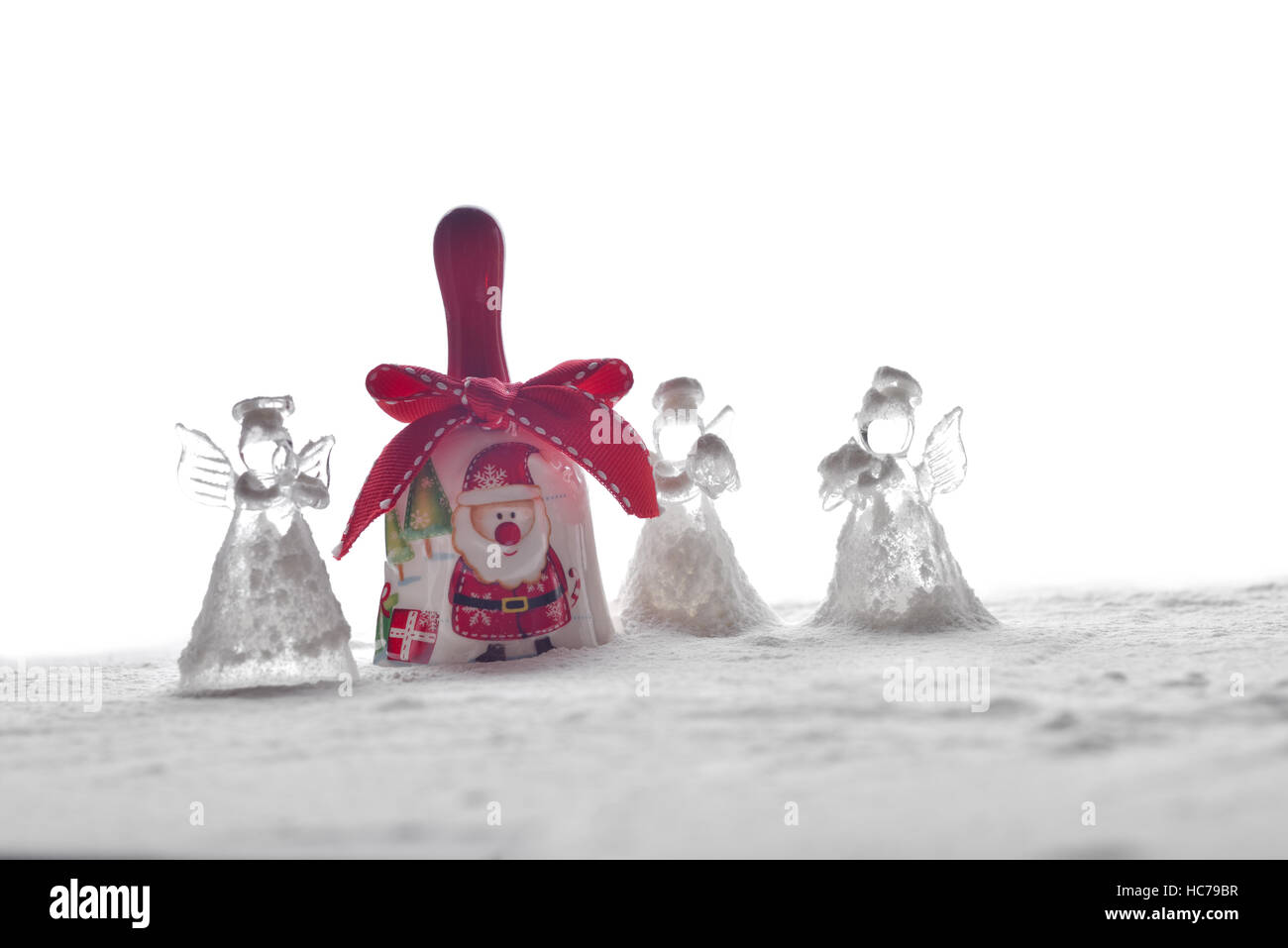 Crystal Angel Christmas Decoration And A Bell With Santa Claus In The Snow  Isolated On White