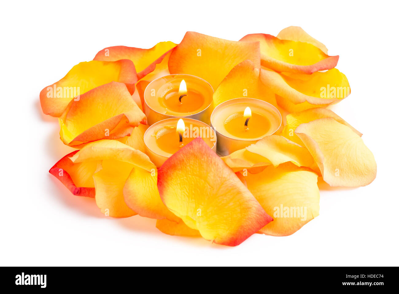 Candlelight And Rose Petals In Orange Color On A White Background Closeup