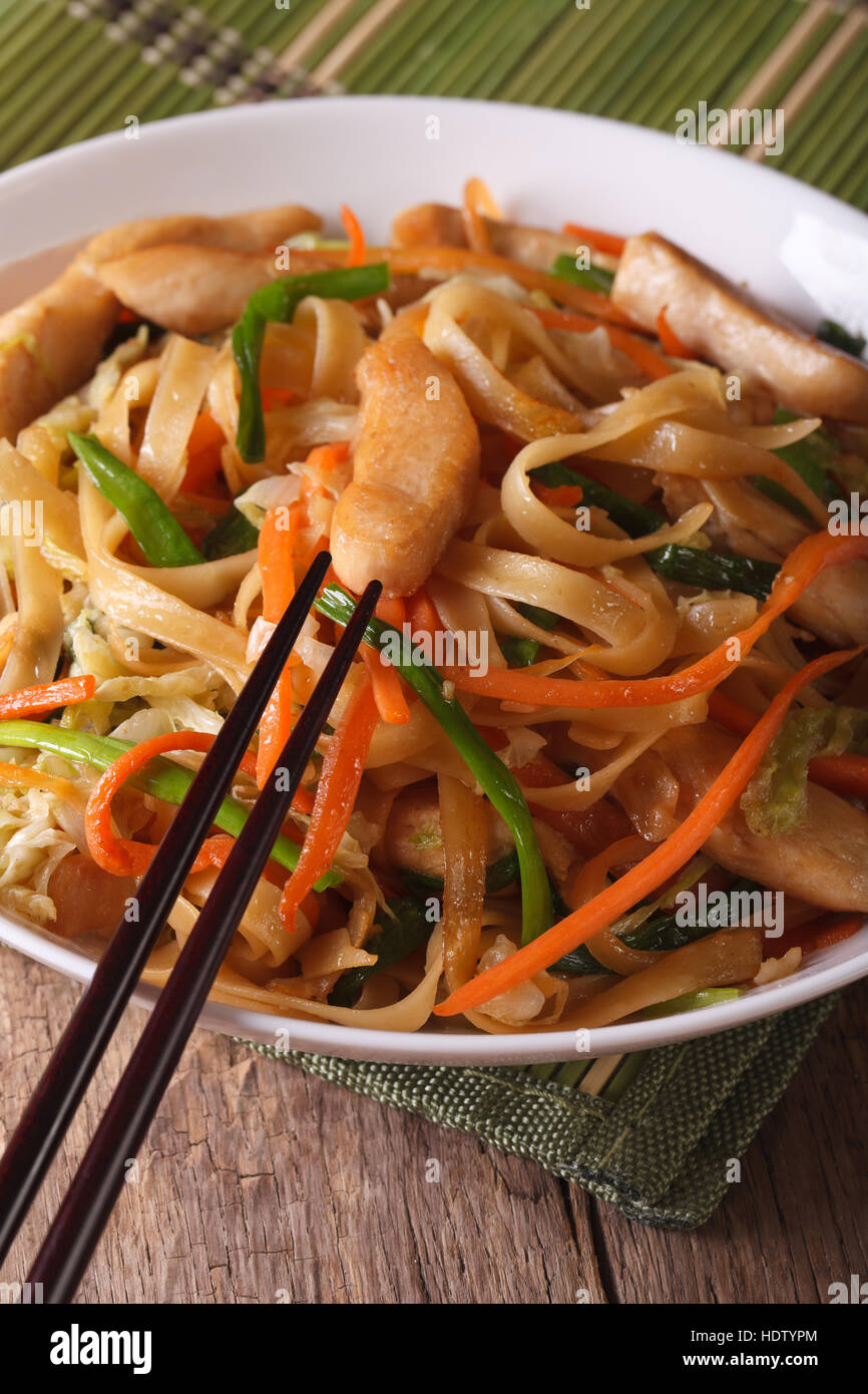 Chinese Food: Chow Mein With Chicken And Vegetables On A Table Close Up.  Vertical