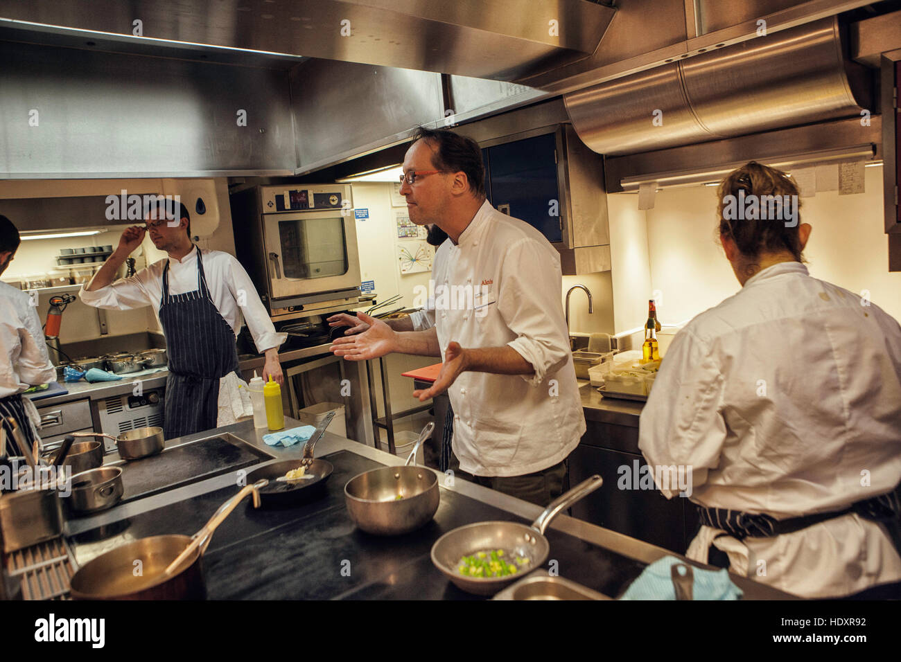 Restaurant Kitchen Staff alexis gauthier, chef and owner of the restaurant, gestures to