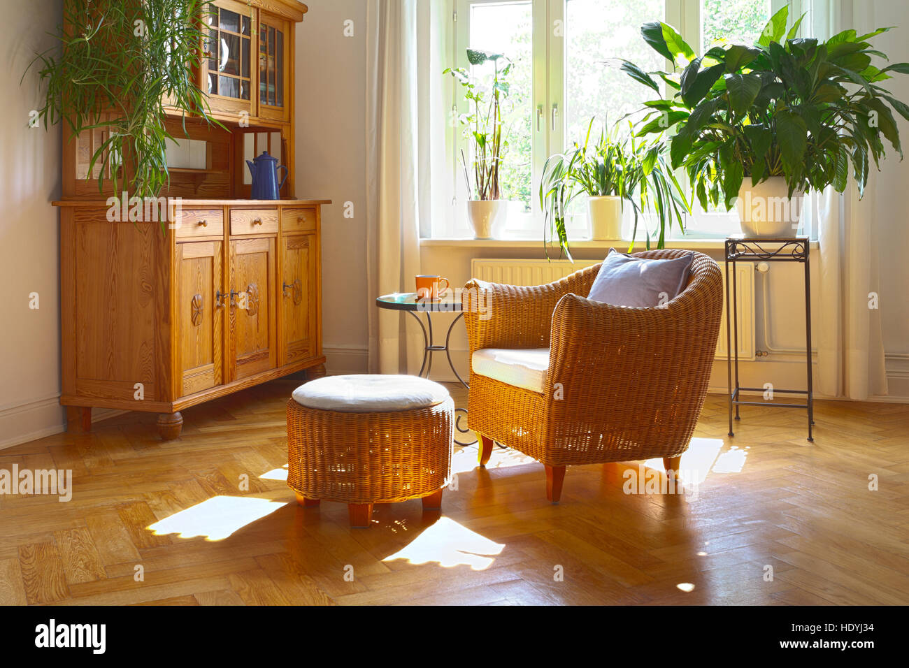 Stock Photo   Sunny Living Room In Warm Colors With Cozy Wicker Armchair  And Stool, Vintage Cupboard, Plants And Large Windows, Nostalgic Part 92