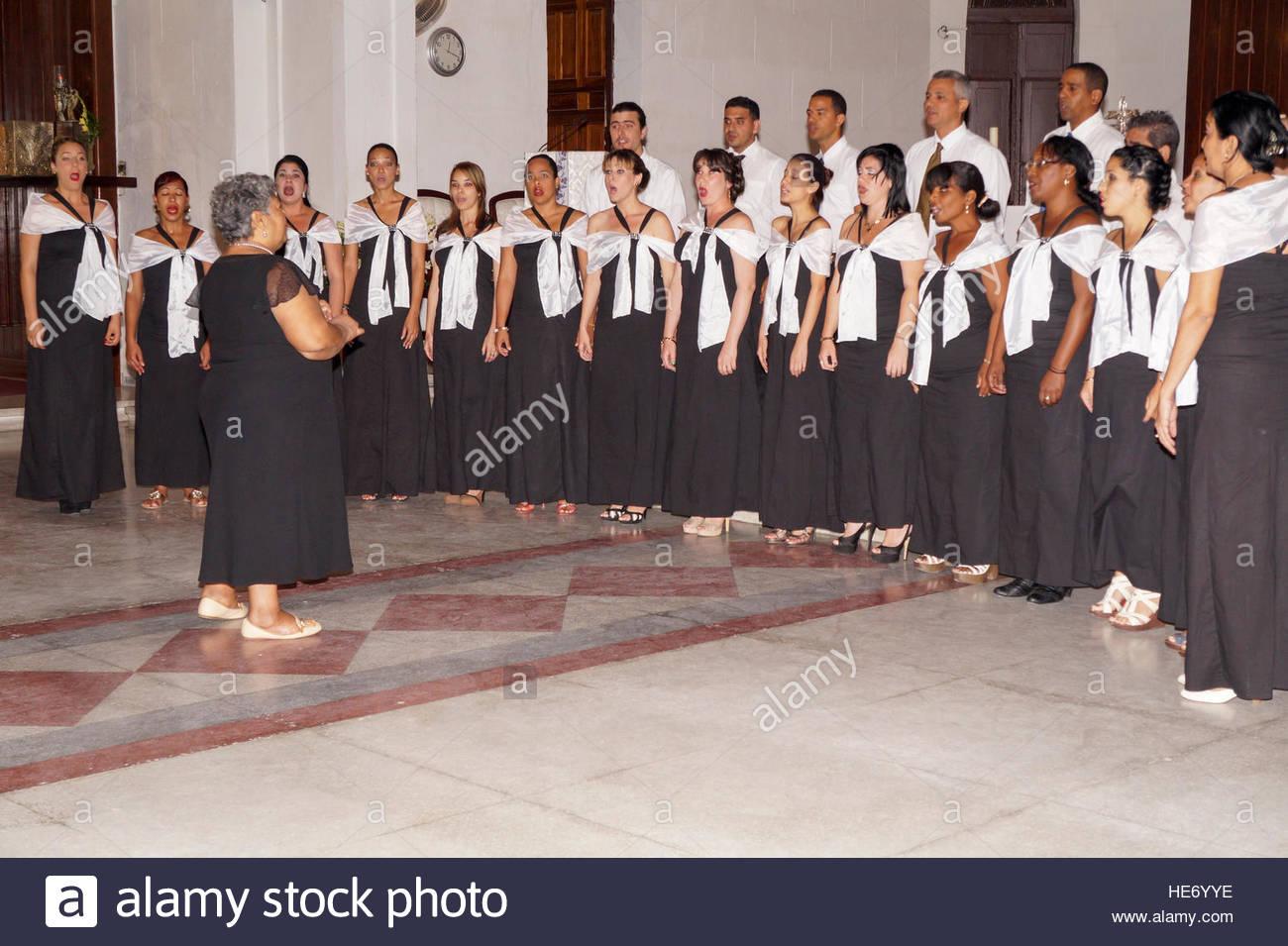 Catholic musical choir in church. Elderly woman directing ...