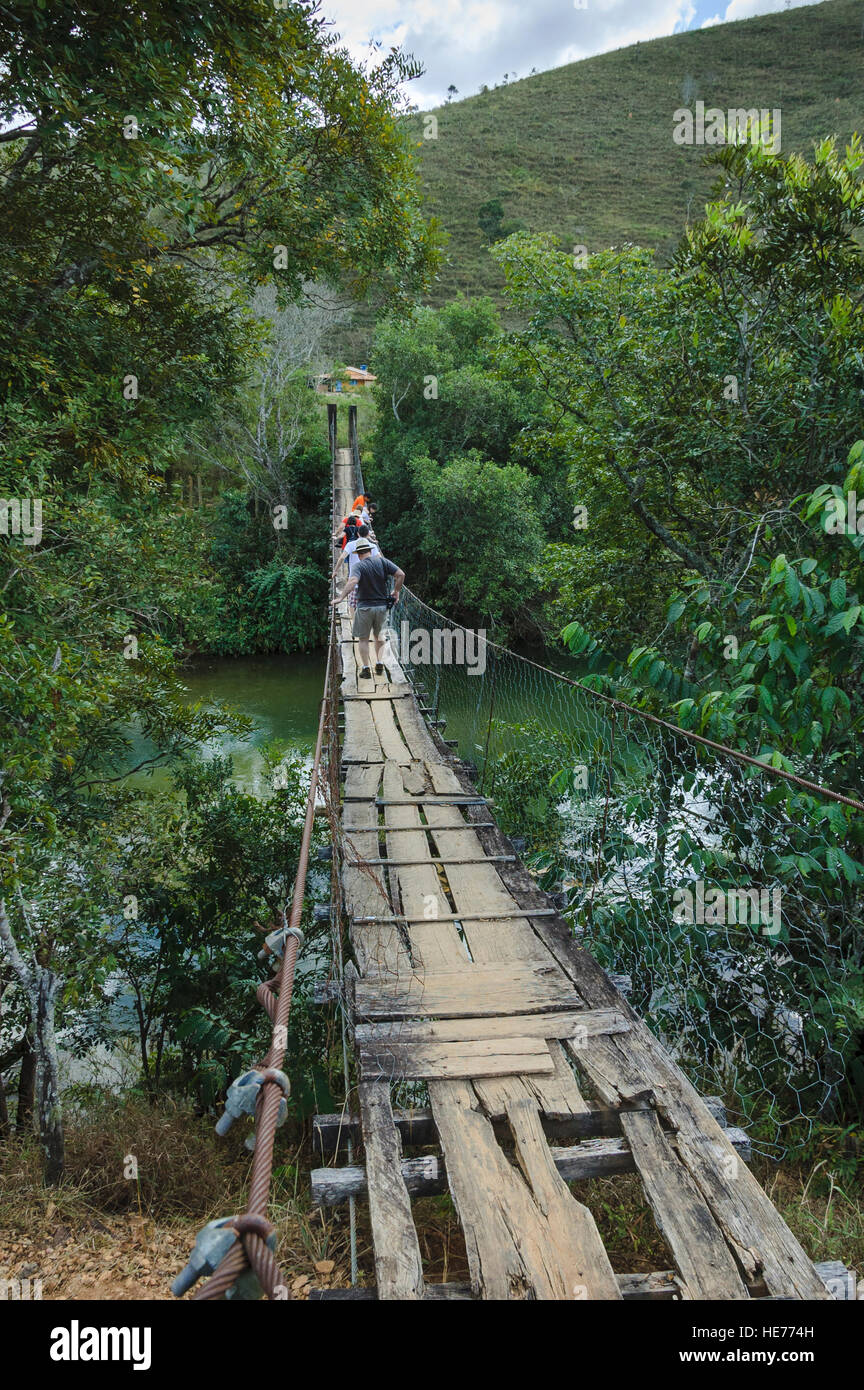 A group of tourists cross a wood bridge in disrepair suspended by ...