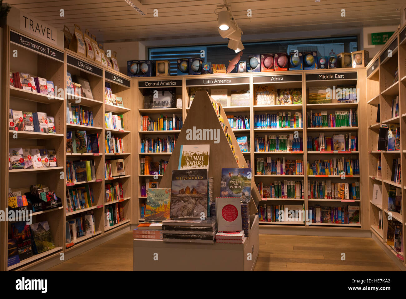 Interior of a modern bookshop with wooden shelves full of books. Section of  travel books and guides