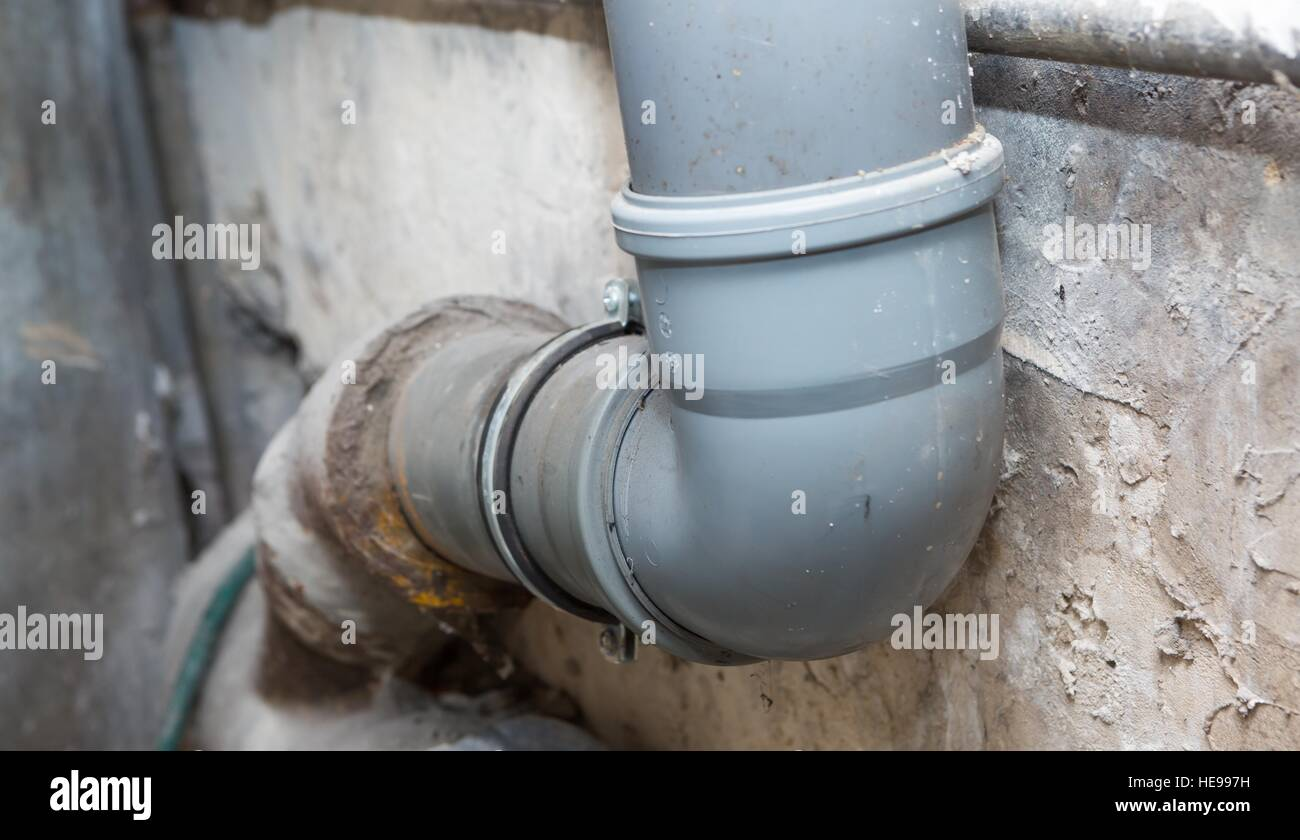 Sewer pipes in home basement  System of gray sanitary pipes in old house. Sewer pipes in home basement  System of gray sanitary pipes in old