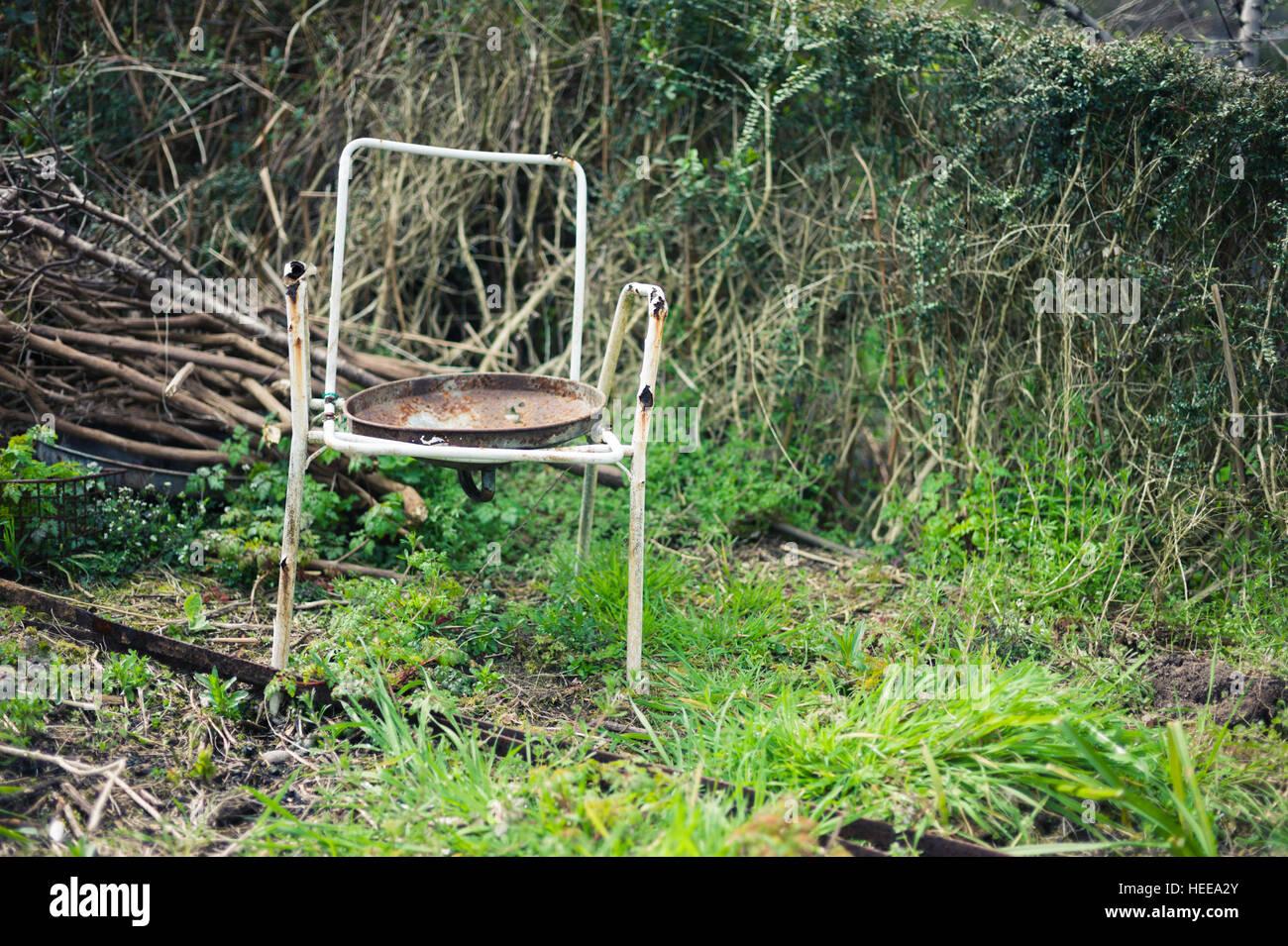 An Old Broken Chair In Overgrown Garden