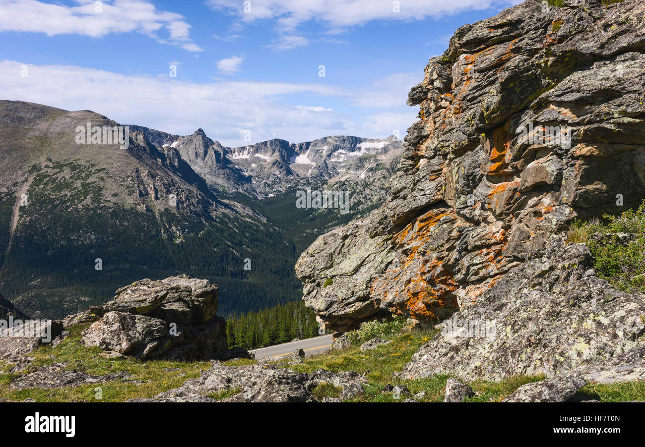 The rocky mountains with large lichen covered boulders and glimpse the rocky mountains with large lichen covered boulders and glimpse of state highway 34 on a bright summer day sciox Image collections