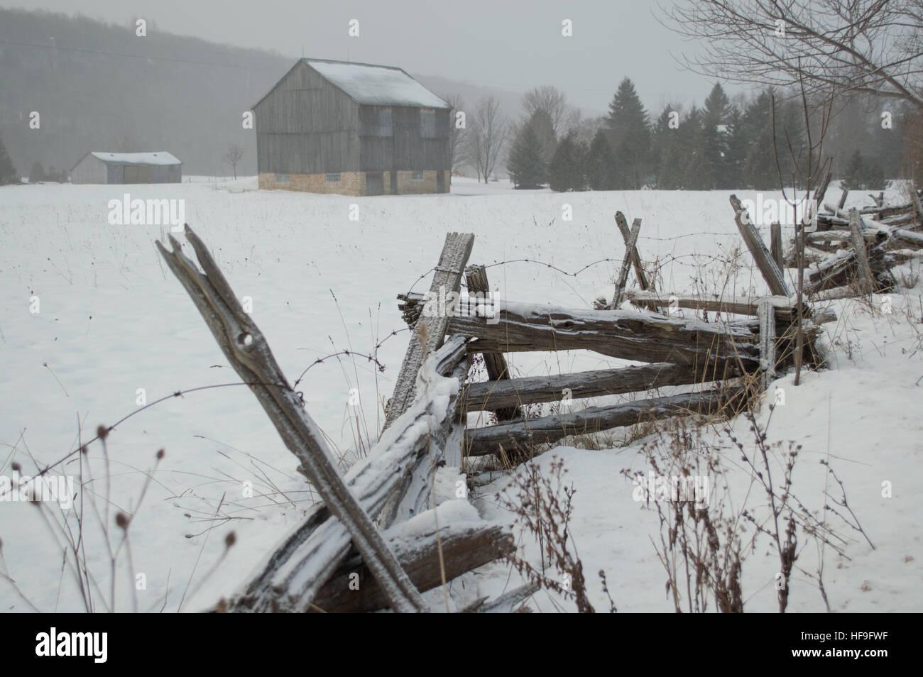 An ontario bank barn with split cedar rail fence in the snow in ...