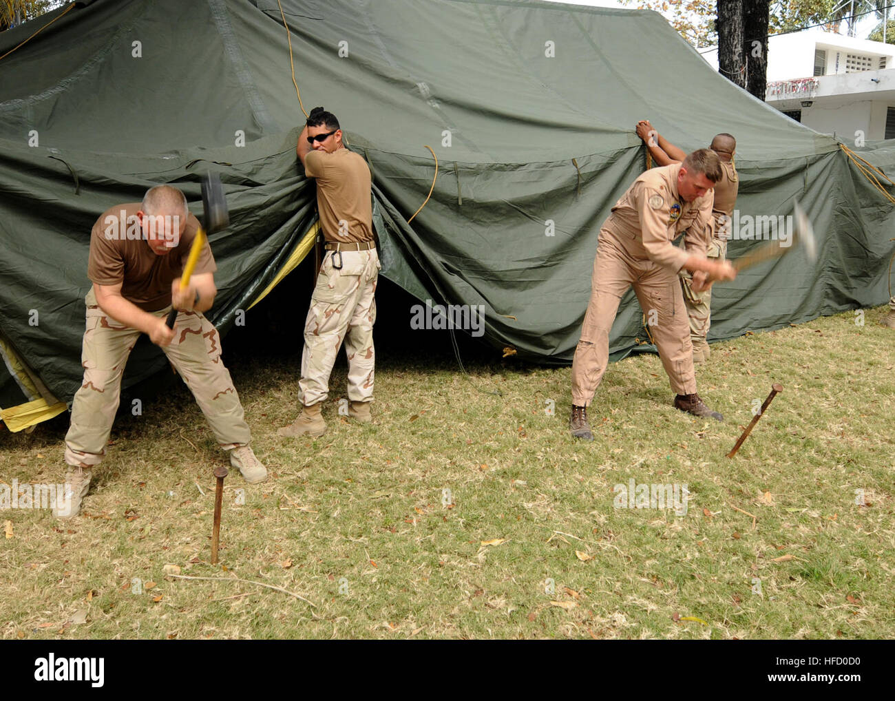 ... assigned to U.S. Coast Guard Port Security Unit 307 and Lt. Cmdr. Andy Grabus from Navy Information Operations Center-Norfolk drive tent stakes into ... & U.S. Coast Guard Chief Petty Officer Brian Coleman assigned to ...