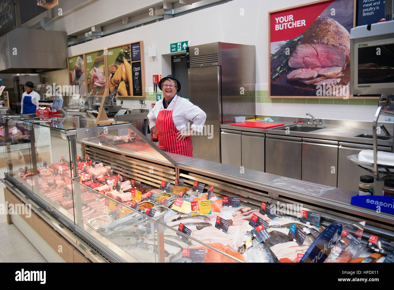 A woman working behind a fresh fish counter in tesco for Fresh fish store