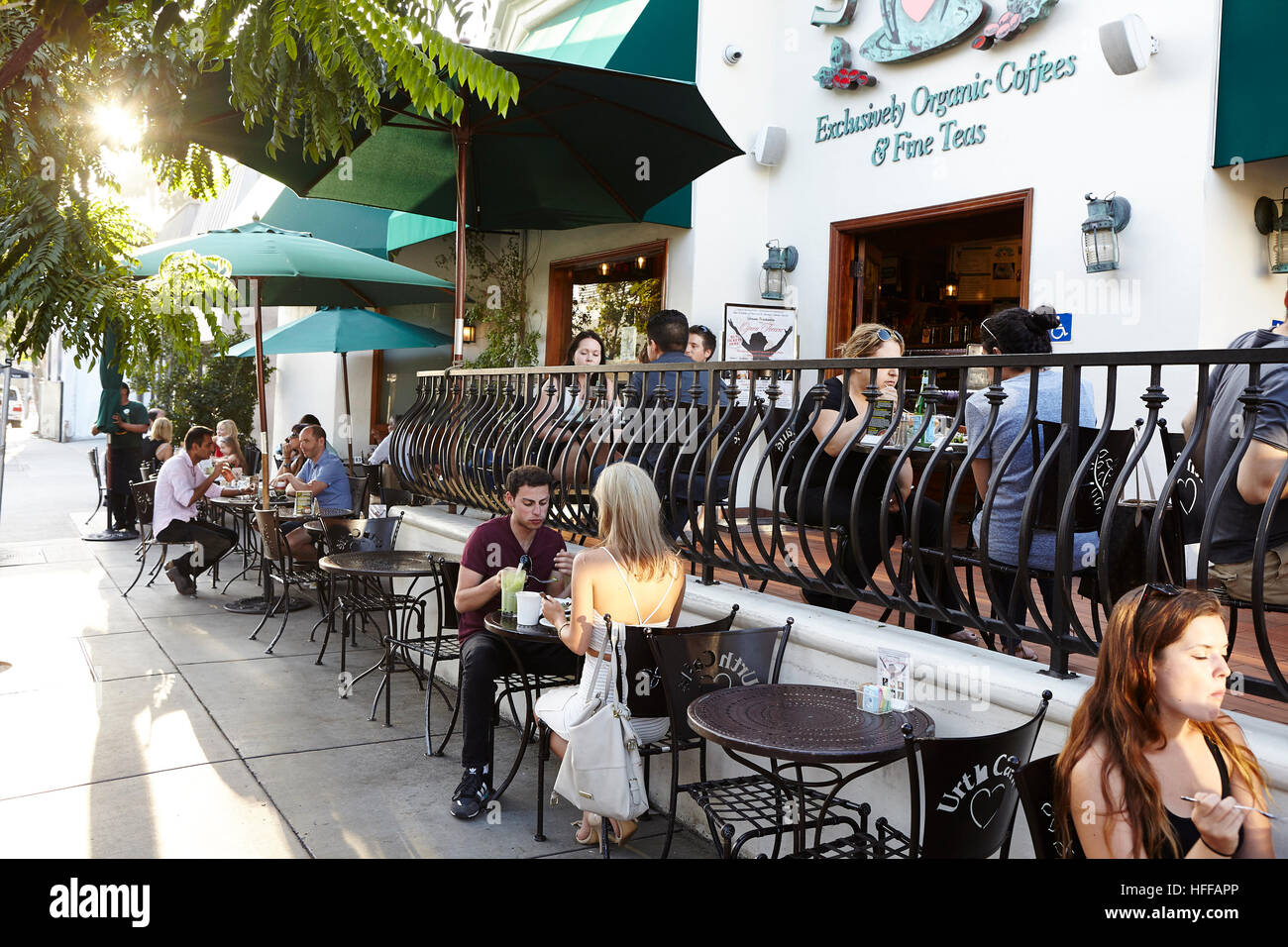 people sitting at cafe table. people sitting on the terrace of urth cafe melrose avenue, los angeles at table