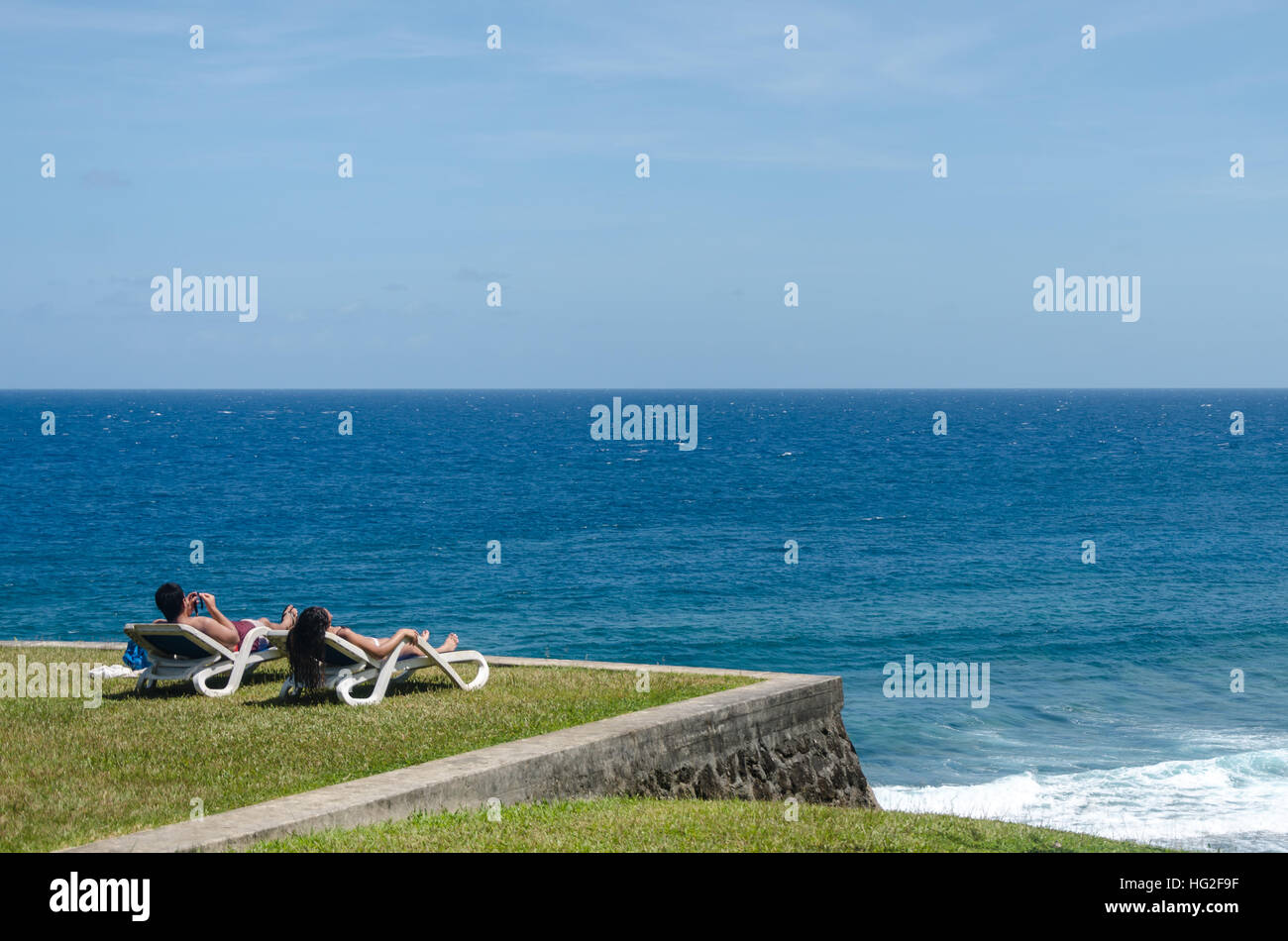 Two People Lying Down On Beach Chairs, Sunbathing In Front Of The Ocean