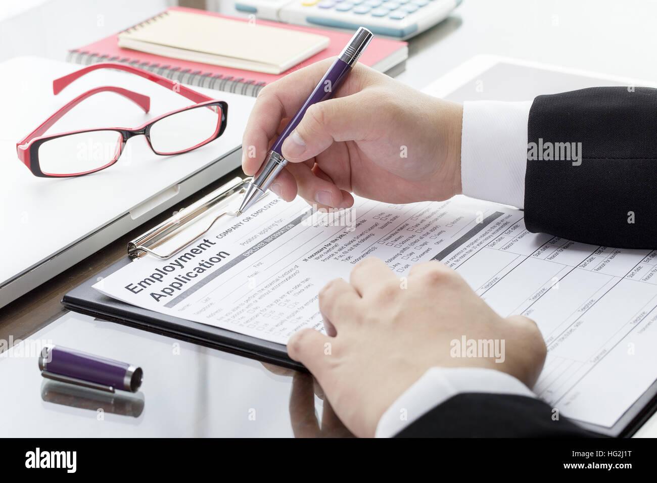 Businessman or job seeker fill in employment application form with businessman or job seeker fill in employment application form with pen job vacancy concept falaconquin